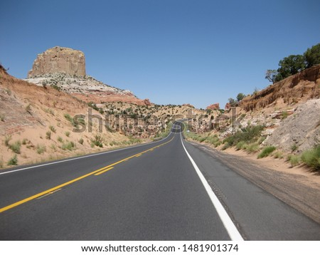 Lonely highway in the high desert in Utah, USA on a bright sunny day. Beautiful red rock lining the road. #1481901374