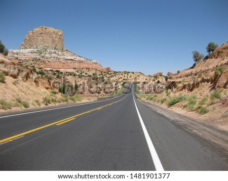 Lonely highway in the high desert in Utah, USA on a bright sunny day. Beautiful red rock lining the road. #1481901377