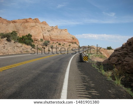 Lonely highway in the high desert in Utah, USA on a bright sunny day. Beautiful red rock lining the road. #1481901380