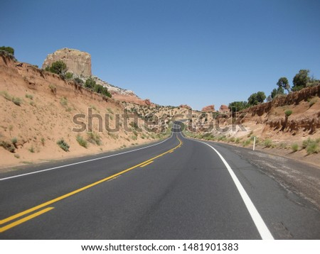 Lonely highway in the high desert in Utah, USA on a bright sunny day. Beautiful red rock lining the road. #1481901383