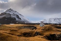 Lonely house on the basalt coast and Stapafell mountain near the snfellsjoekull glacier, Arnarstapi, Snaefellsnes, Iceland