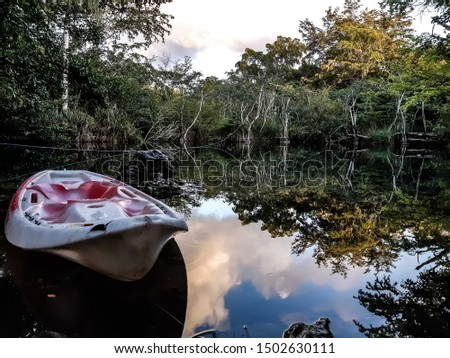 Lonely kayak in a lonely lake with reflection.