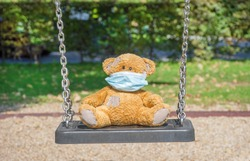 Lonely little teddy bear wearing a medical mask, standing on a swing in the park on a beautiful sunny day. Empty children playground, illness COVID-2019 disease concept