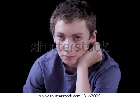 stock photo : Lonely looking teen boy on a black background.