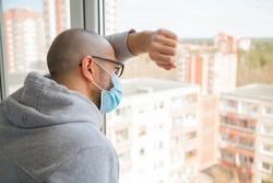 Lonely man in medical mask looking through the window. Isolation at home for self quarantine. Concept home quarantine, prevention COVID-19. Coronavirus outbreak situation