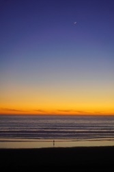 Lonely man in sunset on the coast of Pacific Ocean. Moon in the sky