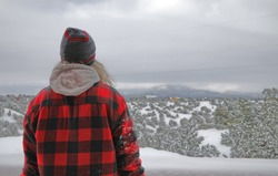 Lonely man in winter clothes, standing with his back to the camera, looks at the snowy desert and the mountain in the distance.