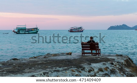 Lonely man on the evening shore of the sea. #471409409