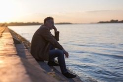 lonely man sitting on stairs next to the river bank