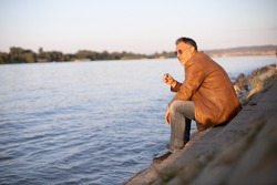 lonely man sitting on the river bank