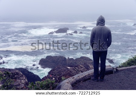 Lonely man standing in front of the pacific ocean and looking at the stormy sea on Vancouver Island.