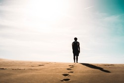 Lonely man stands in desert, footprints, sunny day