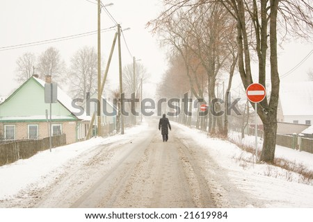 Lonely man walking against traffic flow on a snowy road