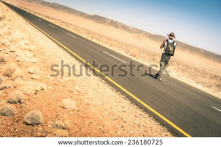 Lonely man walking along the road among the namibian african desert - Concept of alternative lifestyle - Travel trip adventure around the world
