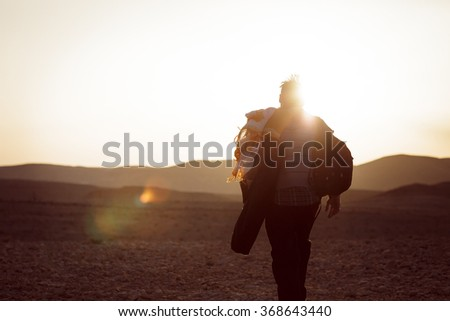 Photo of Lonely man walking in the Negev desert in Israel with strong sunset back light. Color toned image. Hiker walk in a hot stone desert.