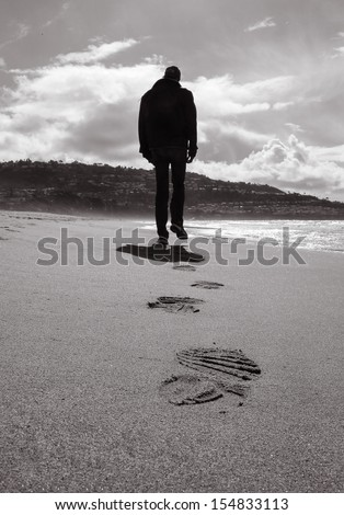 Lonely man walking on a beach (black and white)