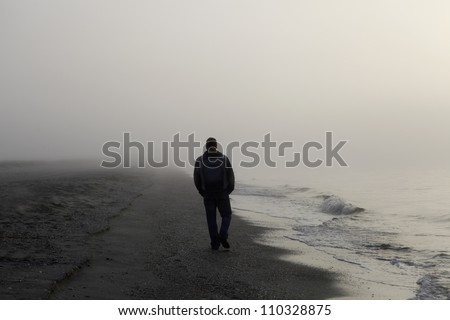 Lonely man walking on a foggy beach