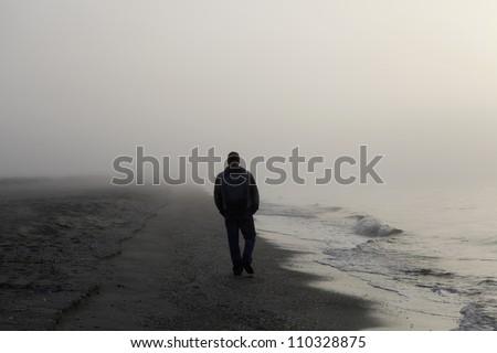 Lonely man walking on a foggy beach #110328875
