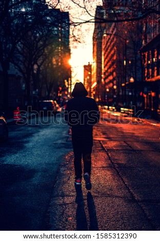 lonely man walking on road with sunset background