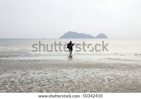 lonely man walking on the beach late afternoon, Thailand