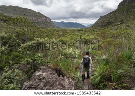Lonely man walking with backpack on a trail in amazing and challenging landscape of Chapada Diamantina mountains. Mucugê, Bahia, Brazil.