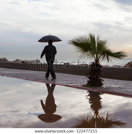 lonely man walking with umbrella under the rain stock