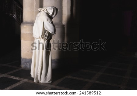 Lonely monk standing at a pillar in a dark medieval church ストックフォト ©