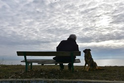 Lonely old man with dog. Senior man sitting on an old wooden bench and watching dark winter see, his dog quietly standing by. Nostalgic mood.