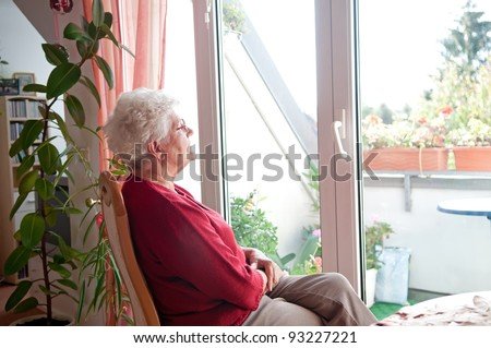 lonely old woman looks out the window