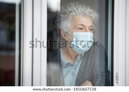 Lonely old woman wearing surgical mask and looking through the window during lockdown. Senior sad woman with face protective mask stay at home. Depressed lady at home during the covid-19 pandemic. Photo stock ©