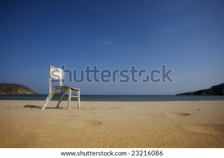 Lonely Old wooden chair on deserted beach
