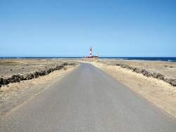 Lonely paved road in arid area towards red and white maritime lighthouse under blue ocean and sky. Lunatic coastal landscape. Detail of architecture and shipbuilding. Maritime safety background.