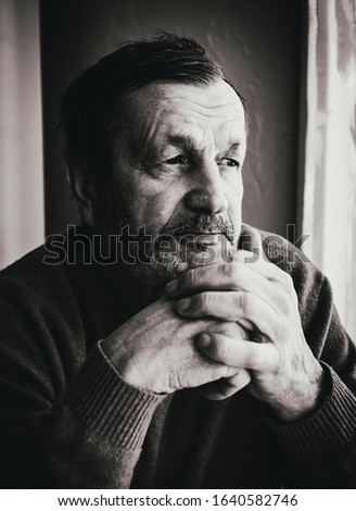 Lonely pensive elderly bearded man indoors black and white portrait