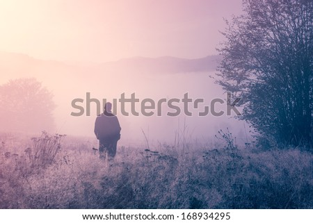 Lonely person in the morning mist. Landscape composition.