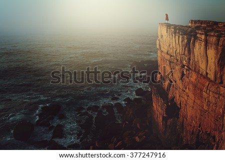 Lonely person on sea cliff. Dark and surreal