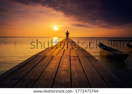 Lonely person standing on a pontoon meditating and enjoying the sunrise or sunset on a lake with a fishing boat on the lake Photo stock ©