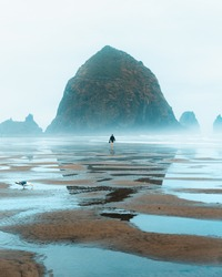 Lonely person walking at the beach towards a giant rock at Cannon Beach in Orgeon in the US.