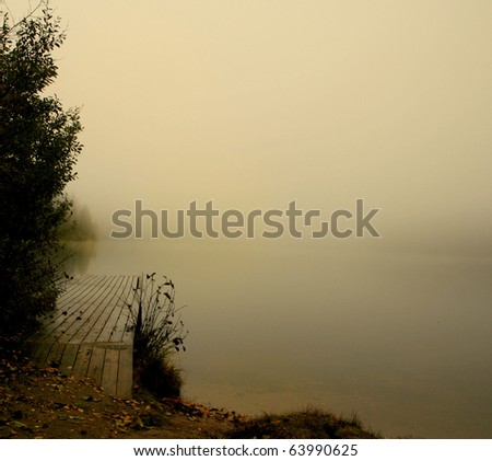 Lonely pier on the foggy lake