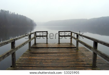 Lonely pier on the foggy lake, tranquil autumn scenery
