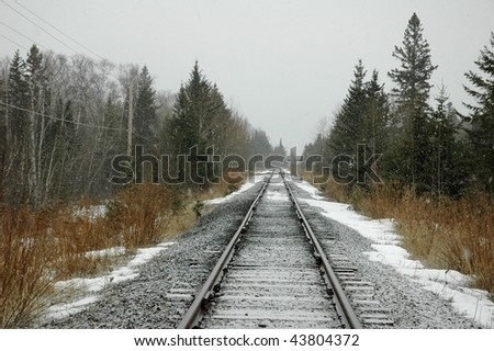 lonely railroad tracks in snow