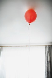Lonely red balloon hanging from the ceiling.