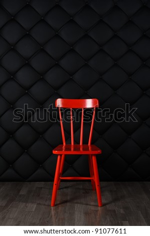 lonely red chair against the black wall
