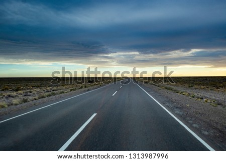 Lonely road at sunset with storm in sight. Lonely road route 3 Argentina #1313987996