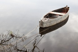 Lonely row boat at lake with Reflection in the water. Wooden fishing boat