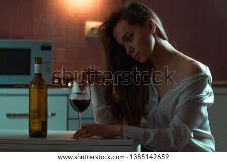 Lonely, sad beautiful young woman in a blouse with alcoholic beverage is drinking alone in evening at home. Female alcoholism and alcohol addiction #1385142659