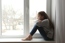 Lonely sad girl at home. The concept of loneliness. saddened alarmed child alone at home.