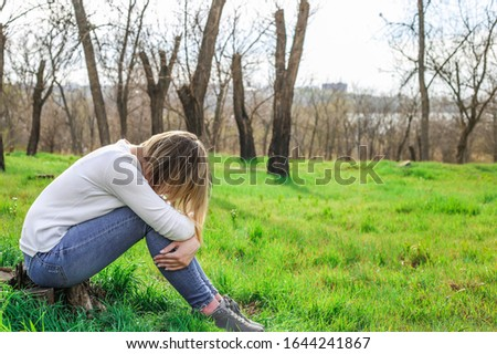 lonely sad girl siting alone in the parkThe concept of lonely thinking and bad mood. The concept of lonely thinking and bad mood