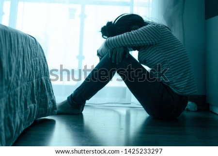 Lonely sad teenager student cry and hug her knees sitting in the dark corner ,Sad girl Unhappy and stressed on bedroom .major depressive disorder concept.vintage tone