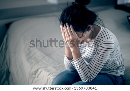 Lonely sad teenager student cry and hug her knees sitting in the dark corner ,Sad woman Unhappy and stressed student on the campus ,Family problems and education.major depressive disorder concept