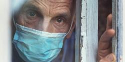 lonely senior man wearing medical face mask looking through window of nursing house closeup